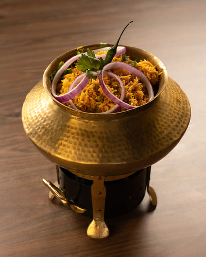 Biryani In a Pot with Onion Rings On It